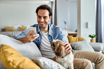 Happy man texting on mobile phone while relaxing with his dog at home.