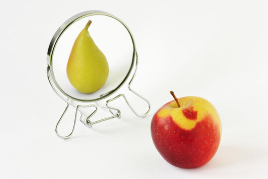 Red apple looking in the mirror and seeing itself as a pear - Concept of dysmorphobia and distorted self-image