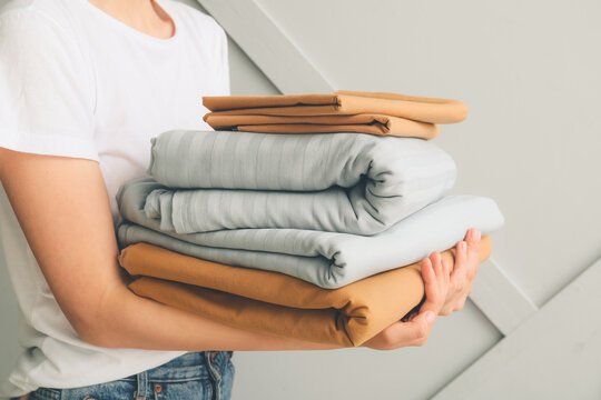 Woman with stack of clean bed sheets on light background