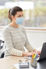 quarantine, remote job and pandemic concept - woman wearing face protective medical mask for protection from virus disease with laptop computer and notebook working at home office