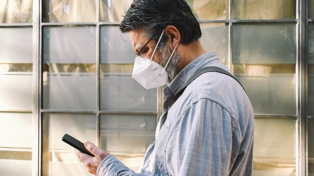 """A middle-aged man wearing a KN95 (or FFP2) face mask consults his mobile as he walks past aehead the window of a closed business. Concept of """"new normality"""""""