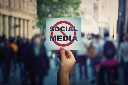 Social media censorship, political war between US president banning social networks. Hand holding a banner with forbidden sign over a crowded street background. Internet communication risk concept.