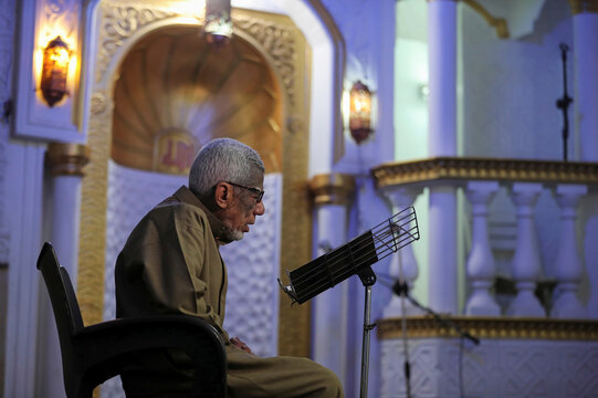 Sa'ed Abdo, 76, Muazzin of Al-Eman mosque reads the holy Koran before praying while the mosque is empty, in Cairo
