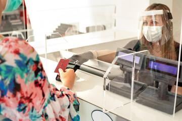 Signora paga alla cassa di un attività commerciale con la carta di credito in cui la commessa indossa una mascherina facciale e una visiera in plexiglass ed è protetta da un pannello trasparente