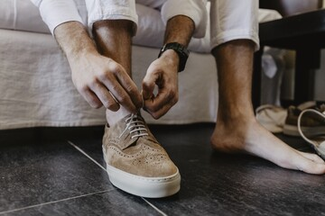 Horizontal shot of a man tying shoelaces of brown shoes