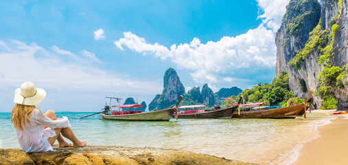 Beautiful woman on paradise Ao Nang Krabi Thailand beach with llongtail boat. Adventure, travel, relax, holiday, vacation, luxury concept.