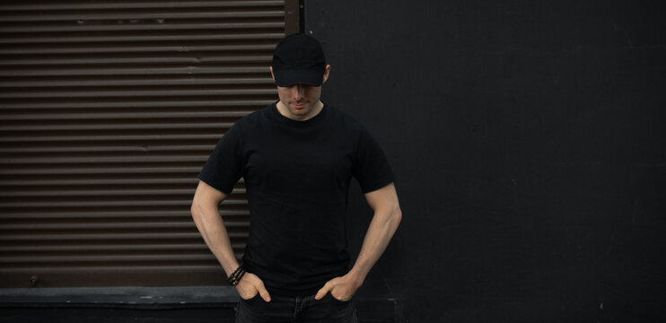 Man in cap and blank t-shirt standing against black wall