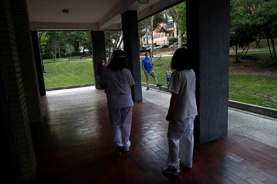 People look at Comunidad de Madrid home care nurses Maria Jesus Santamaria and Ana Arenal as they arrive at an apartment complex to treat a COVID-19 patient in Madrid