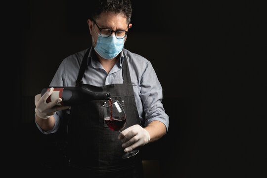 Adult sommelier wearing a coronavirus safety face mask pours red wine into a wineglass. Restaurants reopening concept in phase two after the Covid-19 lockdown.