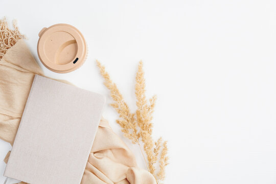 Cozy home office desk with paper notebook, beige blanket, dry flowers and coffee cup on white background. Flat lay, top view. Autumn fall, hygge, nordic style workspace concept.