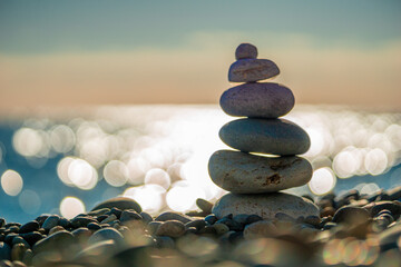 Photo sur Toile Zen pierres a sable Balanced Pebbles Pyramid on the Beach on Sunny Day and Clear Sky at Sunset. Blue Sea on Background Selective focus, zen stones on sea beach, meditation, spa, harmony, calm, balance concept