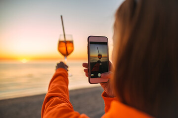 Girl Holding Glass of Drink on Beach at Beautyfull Romantic Sunset Taking Pictures with Phone. Glass and Hand Close Up. View From Back
