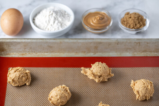 Peanut butter cookie dough balls on a silicon baking mat beside baking ingredients