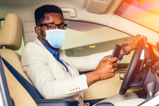 Handsome man in medical mask is standing near his new car and smiling