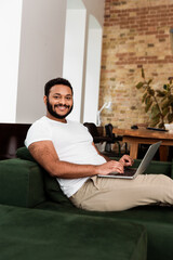 cheerful african american freelancer sitting on sofa with laptop and looking at camera