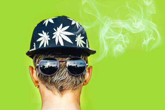 Young girl in sunglasses and cap with leaves of marijuana smokes on a yellow wall background. Hemp smoke puffs