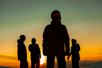 Four people wearing ski suits, goggles and helmets silhouetted against a sunset.