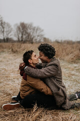 A white man and black woman sitting in a wintry rural landscape hugging and touching noses.