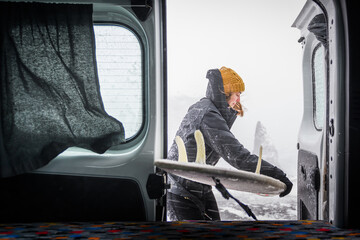 Woman with a black jacket and woolly hat putting a surfboard into the back of a campervan. Winter Surfing
