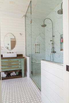 Bathroom with marbelled tiledand glass shower cubicle, wooden vanity unit with handbasin against cream wood panelled wall.