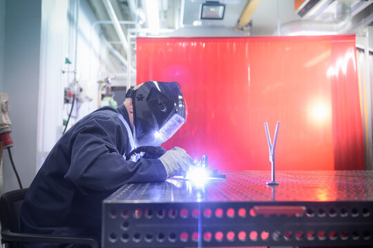 A student wearing overalls and a welding mask working at a workbench.
