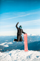 A person wearing a black ski suit, helmet and goggles jumping for joy on top of a mountain on a red snowboard.