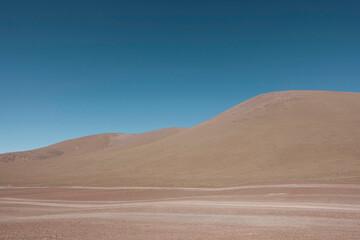 View across a desert landscape towards a large dune.