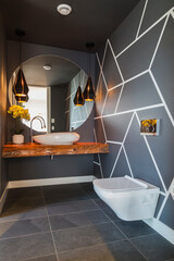 Interior view of modern bathroom with dark grey floor tiles and walls with geometric pattern, round wall mirror over basin on wooden railway sleeper and wall mounted toilet.