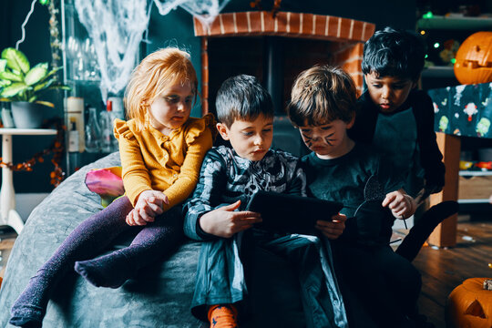 Four children sitting on a beanbag looking at a computer tablet.