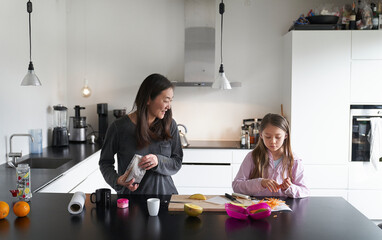 Home life, a school morning during lockdown. A girl and her mother in a kitchen cooking together