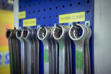 Close up of spanners hanging on a rack.