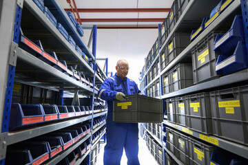 Man holding a storage box in a shelved storage area.