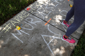 Chalk markings done by protesters cover the sidewalk outside the Florida home of former Minneapolis police officer Derek Chauvin, in Orlando