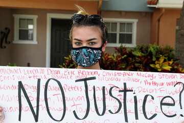 A protester holds a placard outside the Florida home of former Minneapolis police officer Derek Chauvin, in Orlando