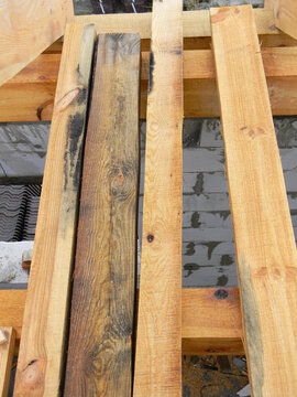 A close-up on rotten, damaged with mold and mildew wood, boards, timber and new untreated timber boards, planks on a brick house construction.