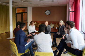 Male and female entrepreneurs discussing while sitting in circle during office workshop