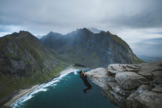 Man hanging off cliff at Ryten mountain in Lofoten Islands
