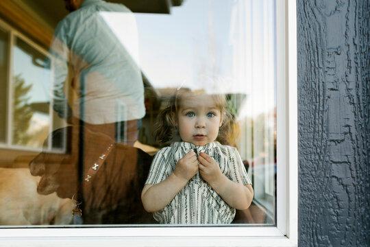 Girl†(2-3)†looking through window