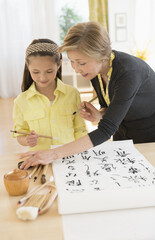 Grandmother and granddaughter (8-9) painting japanese symbols