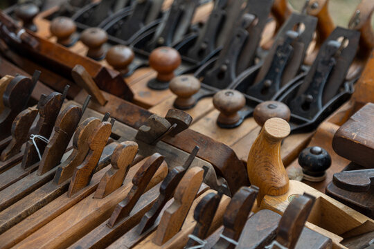 An angular, slightly overhead perspective of a collection vintage woodworking planes on a table