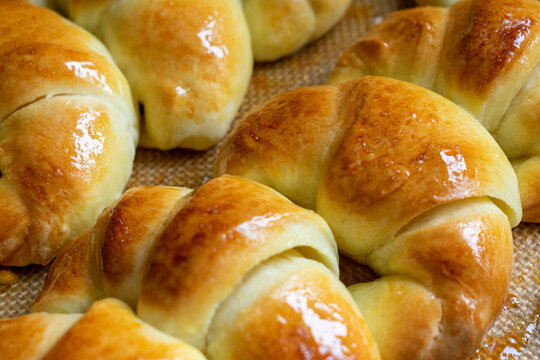 Argentine croissants, medialunas de Manteca over silicon pastry mat close-up