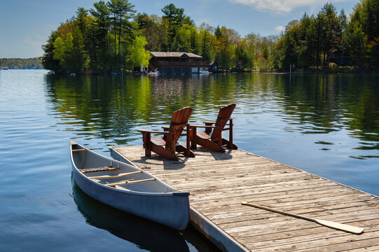 Two Muskoka chairs sitting on a wood dock facing a lake. Across the calm water is a brown cottage nestled among green trees. A canoe is tied to the dock.