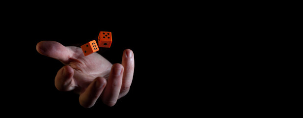Two orange dice cubes thrown in the air above caucasian male hand against black background - narrow banner with copy space