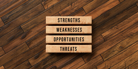 cubes with the words STRENGTH, WEAKNESSES, OPPORTUNITIES and THREATS on wooden background