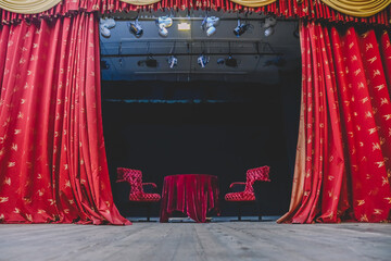 The backstage of the theater, with a table and chairs in the center.