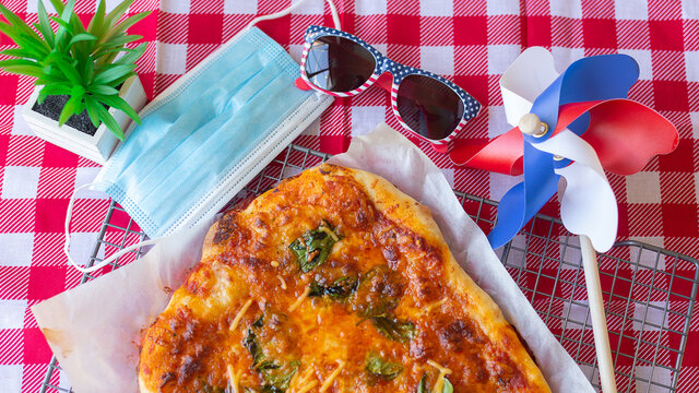Picnic for Independence Day the USA. Homemade pizza cooked by a child on a red tablecloth, sunglasses with the flag of America and a medical mask. Daylight.