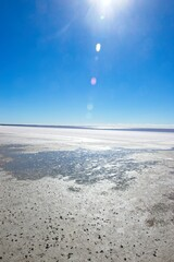 Vast salt lake in outback desert of Western Australia, with sunny glare, blue sky and horizon as background and copy space.