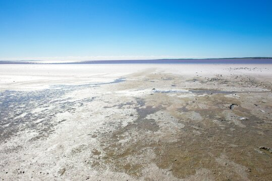 Panoramic landscape view of scenic salt lake in outback desert of Western Australia, with sunny glare, blue sky and horizon as background and copy space.