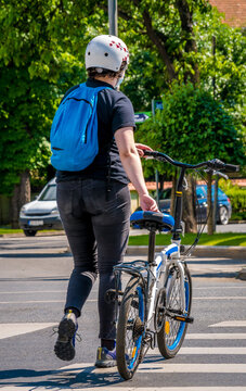 Man with a bicycle crossing the street. Man walking beside his bicycle, the right way to croos the road with a bicycle.