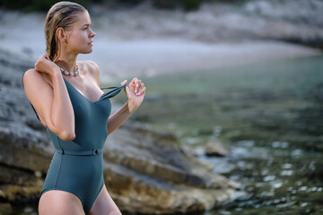 Photo of beautiful boho styled model wearing green swimsuit and  bohemian jewelery on the beach in sunset